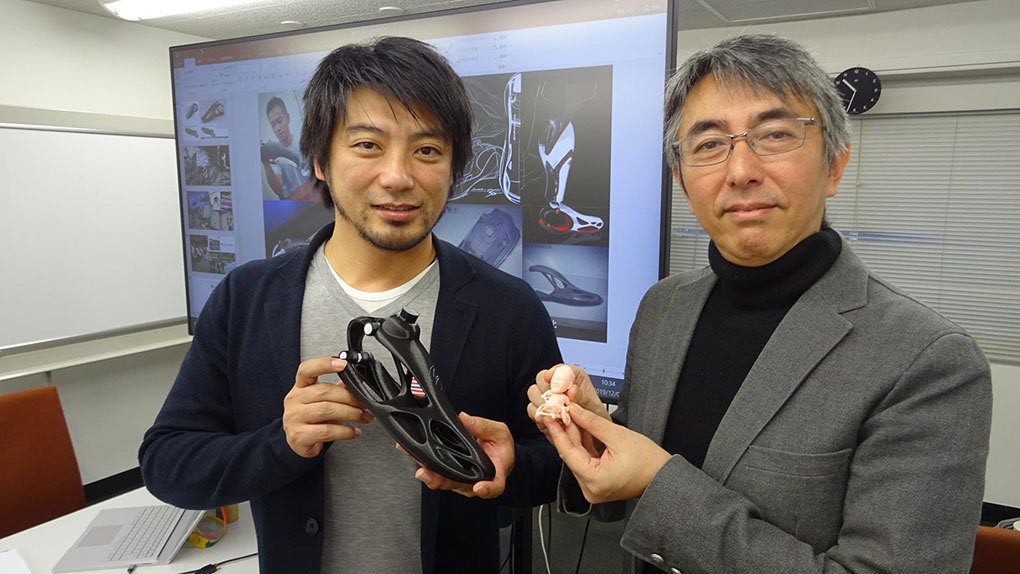 試作品の足を持つのが坂田功氏(左)、眞田選手のフィギュアを持っているのが青木省吾氏(右)